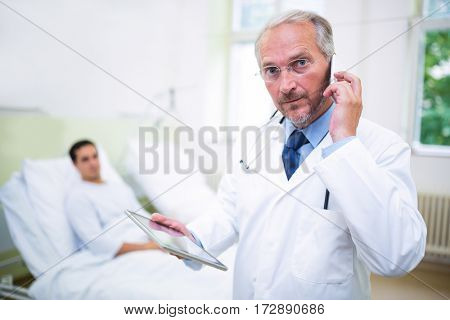 Doctor talking on mobile phone and talking on mobile phone in hospital