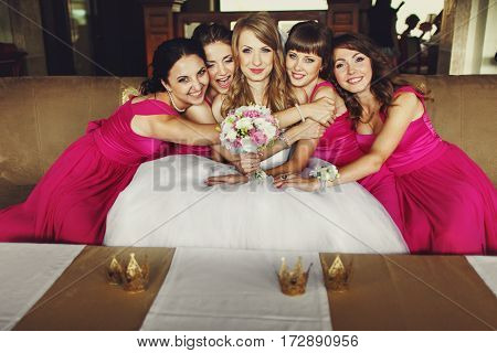 Bridesmaids In Pink Dresses Lean To A Pretty Bride Sitting On The Sofa