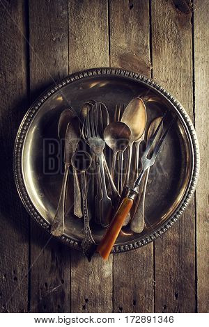 Vintage Old Rustic Kitchen Utensils Forks Spoons and Knifes on Old Wooden Table. Food or Vintage Rustic Concept. Top View.