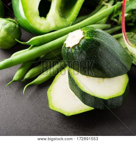 Fresh zucchini with assorted green vegetables, salad, peas and Brussels sprouts on brown stone table top. Healthy food concept with copy space.