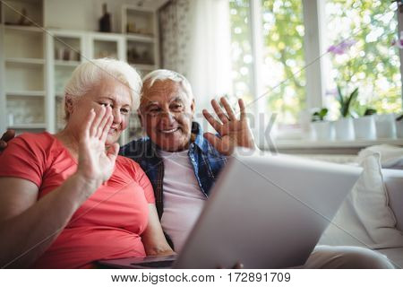 Senior couple video chatting on laptop at home