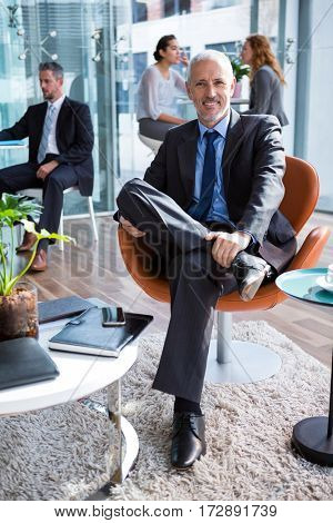 Portrait of smiling businessman sitting on chair in office