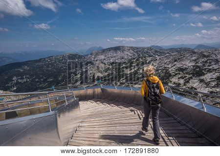Woman going down the stairs on the sight in Alps, Dachstein mountain