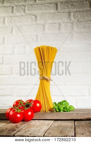 Tasty Fresh Colorful Italian Food Raw Spaghetti on Kitchen Table on Kitchen Background. Cooking or Healthy Food Concept.
