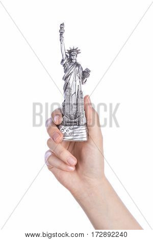 Hand holding a Statue souvenir toy on white background. Metal decoration.