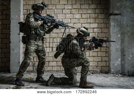 Pair of US Army Rangers with machinegun and rifle moving along the wall after each other on military mission