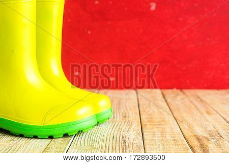 Yellow gumboots on wooden old background wall