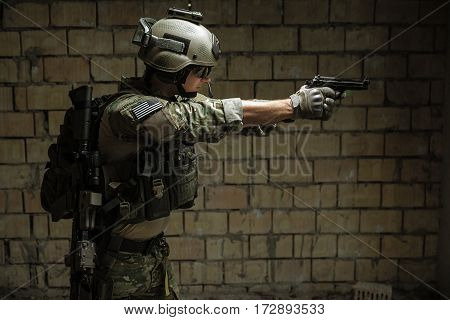 US Army Ranger aiming pistol with two hands. Shooting stance and grip. Side view