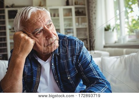 Worried senior man sitting on a sofa at home