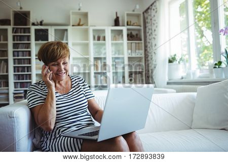 Senior woman talking on mobile phone while using laptop in living room at home