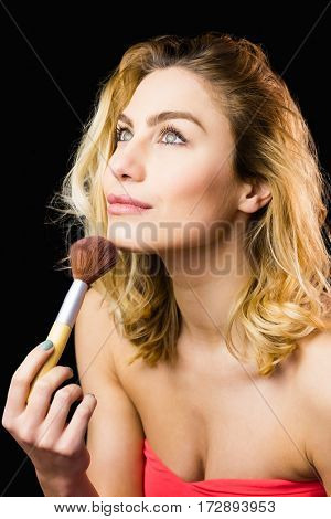 Close-up of beautiful woman posing with make-up brush against black background