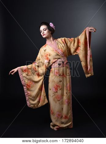 Dancing Woman In Traditional Japanese Kimono On Black Background