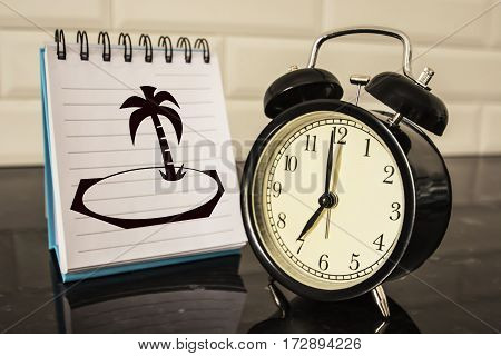 An alarm clock and a picture of the island on the Notepad sheet . The concept of time given for relaxation and vacation
