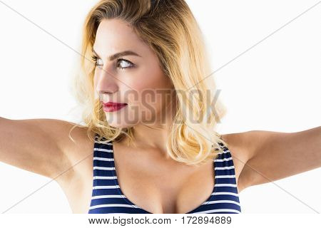 Close-up of beautiful woman posing with arms outstretched against white background