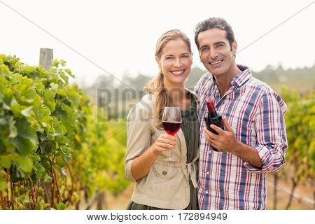 Portrait of happy couple holding glass and a bottle of wine in vineyard