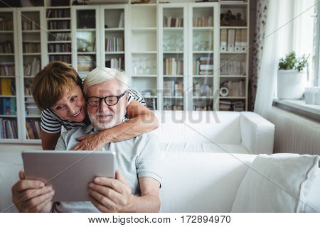 Senior couple using digital tablet in living room