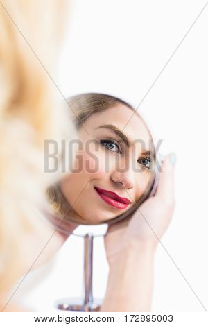 Reflection of beautiful woman in hand mirror against white background