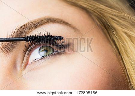 Close-up of beautiful woman applying mascara on eyelashes
