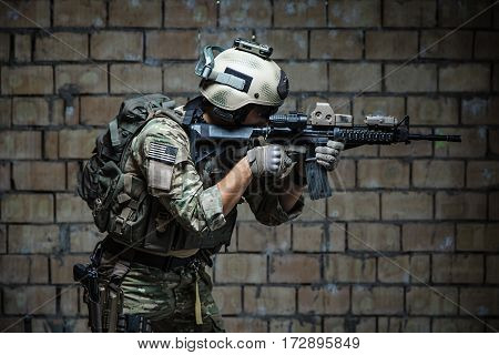 US Army Ranger aiming rifle with two hands. Shooting stance and grip. Side view