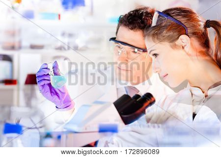 Life science researchers observing solution in laboratory. Chemical lab. Attractive young PhD student and her post doctoral supervisor scientist observing blue indicator color shift after in flask.