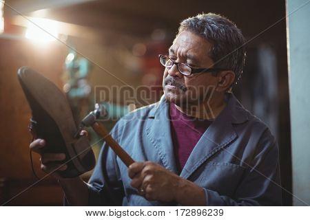 Shoemaker hammering on a shoe in workshop