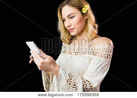 Beautiful woman using mobile phone against black background