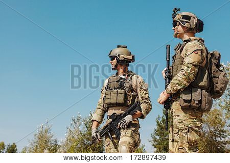 US Army Rangers with weapons in the desert. Plate carriers, eyewear goggles and combat helmets are protecting them