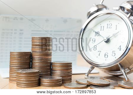 Concept business finance save money Coins stack on wood table with book bank and alarm clock