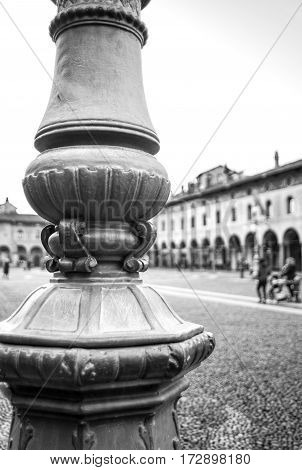 The reinassance square of Vigevano, names Ducale, with a characteristic street light. Black and white photo.