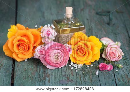 Still life with colorful roses and a gift on an old shabby wooden table for mothers day