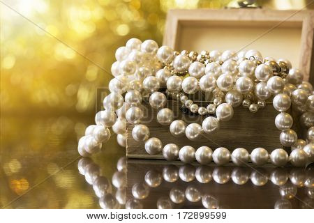 White and golden pearls jewelry gift background