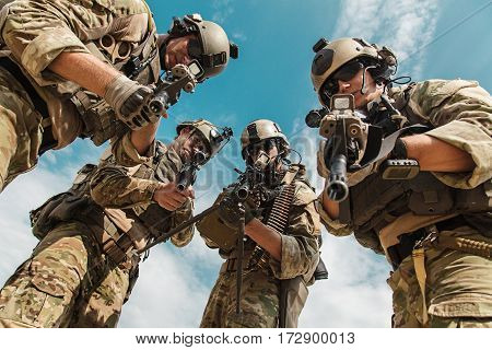 US Army Rangers pointing weapons to the camera detaining person. Low angle view