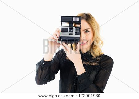 Beautiful woman clicking photo from camera against white background