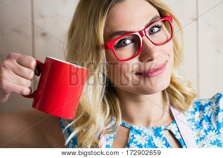 Close-up of smiling woman holding a coffee mug against texture background