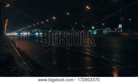 City traffic in the night. Winter, the road is wet.