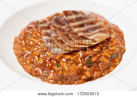 Rye risotto with grilled meat slices in deep porcelain plate