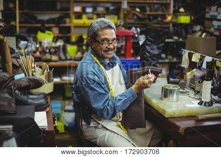 Portrait of smiling shoemaker applying glue on shoe in workshop
