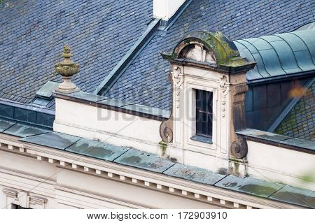 Old roof with vintage windows and ornamental cornice.