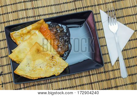 fresh fried pancakes on a rectangular plate with apple jam
