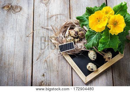 Happy holidays easter spring festive decoration. Yellow primula primrose flowers in a pot, home house chalkboard and quail eggs in a nest on a rustic wooden background. Copy space