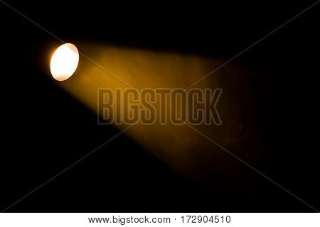 Authentic beam of light from reflector in theatre smoke colored on yellow orange and red colours.