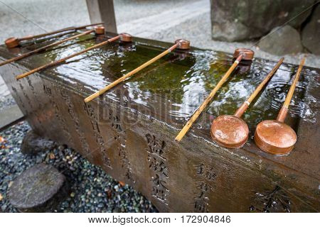 KAMAKURA, JAPAN - NOVEMBER 8, 2016: Water purification at entrance to the buddhist temple of Kamakura, Japan. Monumental outdoor bronze statue of Amida Buddha is one of the most famous icons in Japan.
