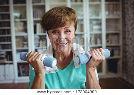 Portrait of senior woman exercising with dumbbells at home