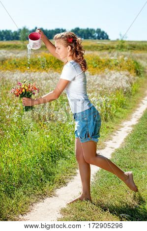 Pretty young woman with a bouquet of wild flowers outdoors. Beautiful blonde girl walking barefoot on summer field