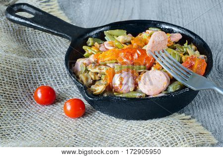 Fried vegetables with chopped sausage in a cast iron pan, a piece on a fork. Gray wood background, burlap and selective focus.