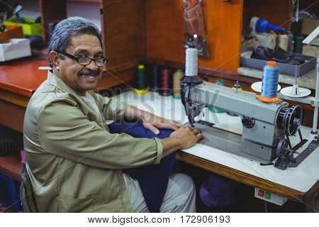 Portrait of smiling shoemaker using sewing machine in workshop