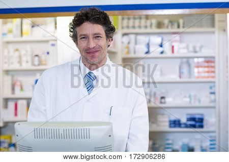Portrait of smiling pharmacist standing at counter in pharmacy