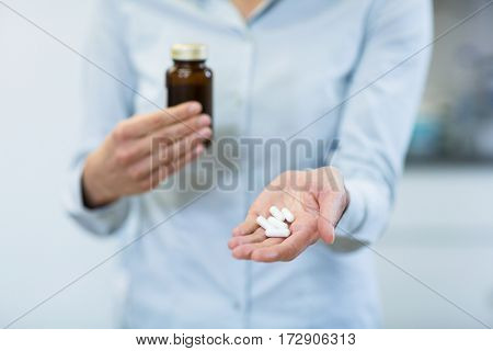 Mid-section of pharmacist holding a medicine bottle and pills in pharmacy