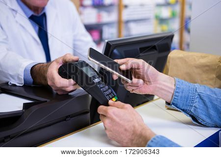 Customer making payment through smartphone in payment terminal at pharmacy