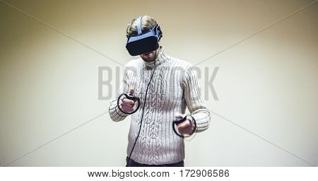 Man in helmet virtual reality plays game. Man uses VR-headset display with headphones for virtual reality game in office. High-tech devices. Augmented reality device creating virtual space